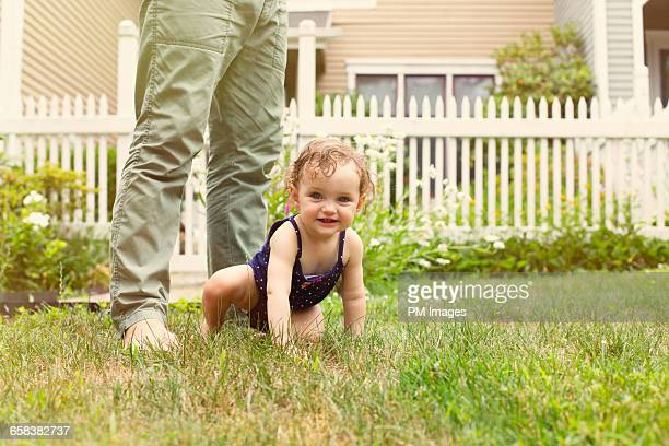 Baby girl at father's feet on front lawn