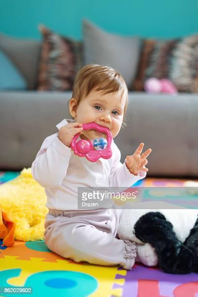 Baby girl biting her toys