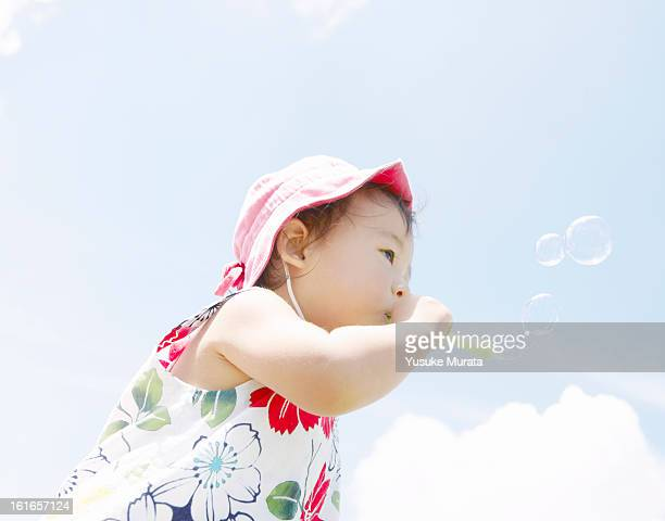 Baby girl blowing bubbles