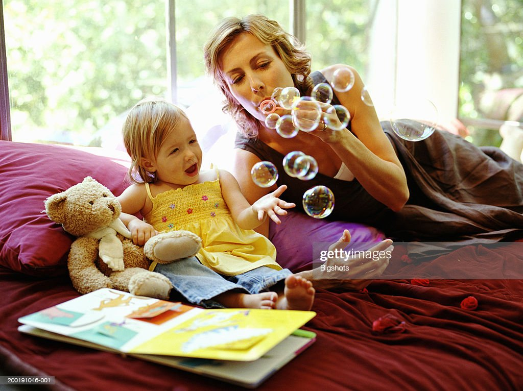 Baby girl (15-18 months) catching bubbles blown through wand by mother : Stock Photo