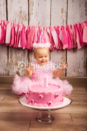 A Baby Girl Celebrating Her First Birthday With Pink Cake Stock Photo
