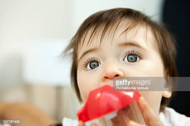 Baby girl chewing on plastic cup
