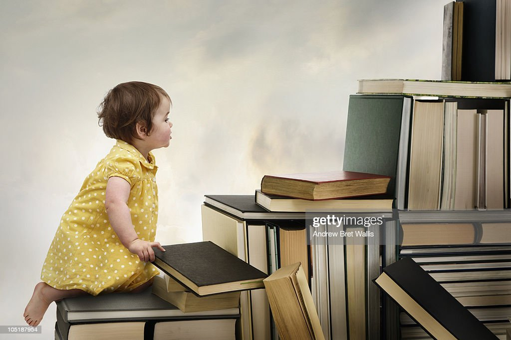 Baby girl climbing a staircase of books