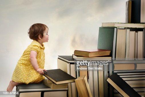 Baby girl climbing a staircase of books : Stock Photo