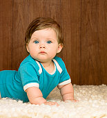 Baby girl (6-9 months) crawling on rug, portrait