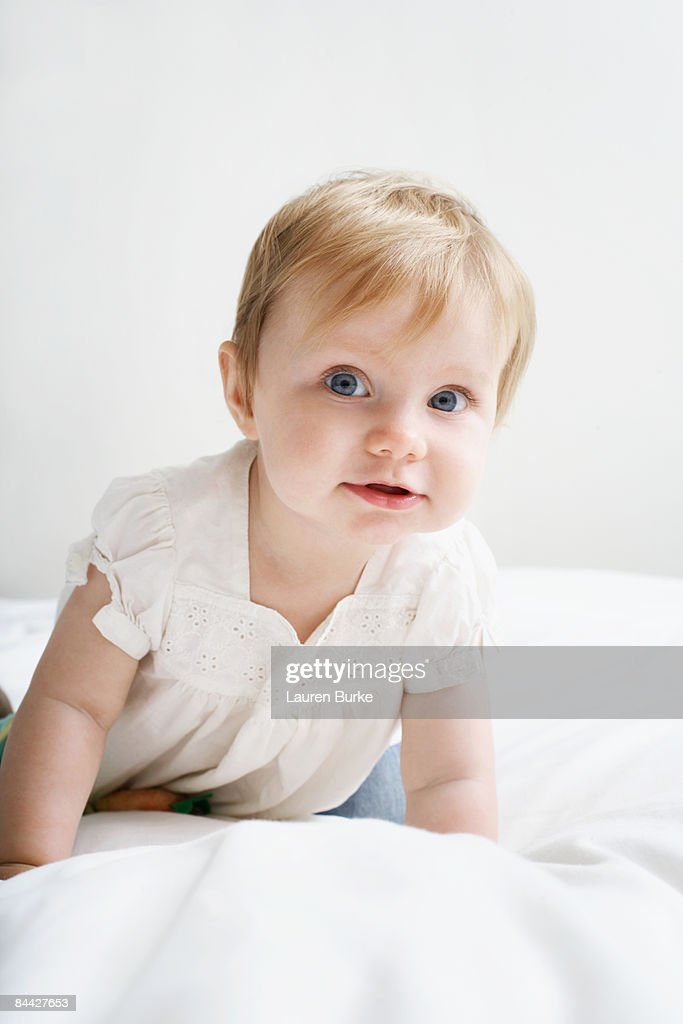 Baby Girl Crawling on White Bedding