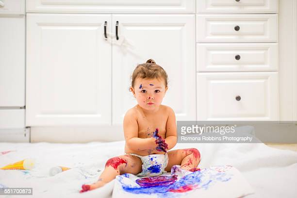 Baby girl dabbling with finger paints in white kitchen
