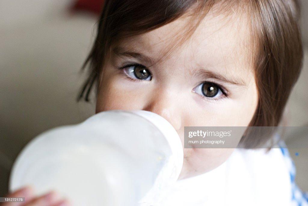 Baby girl drinking bottle : Stock Photo