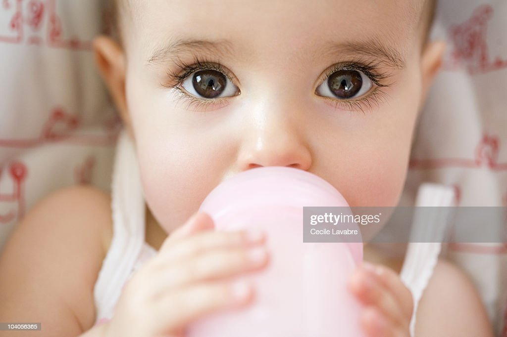 Baby girl drinking from bottle : Stock Photo
