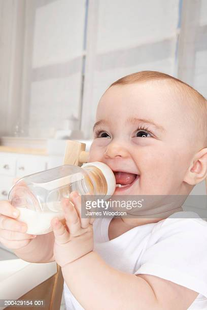 Baby girl (5-7 months) drinking milk from bottle, smiling