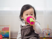 baby girl drinking water using a cup