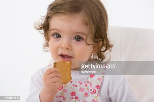 Baby girl eating cookie, close up : Stock Photo