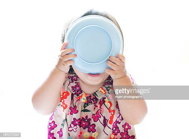 Baby girl eating out of bowl