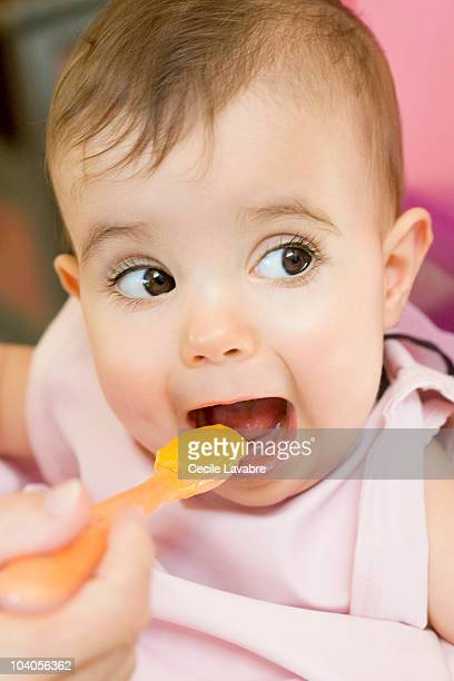 Baby girl eating pureed food from spoon