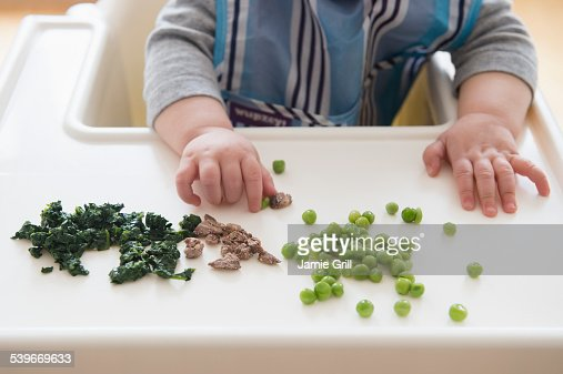 Baby girl (12-17 months) eating steak, spinach and green peas