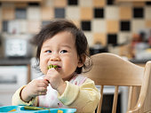 Asian baby girl eatin  vegetable first time at home kitchen