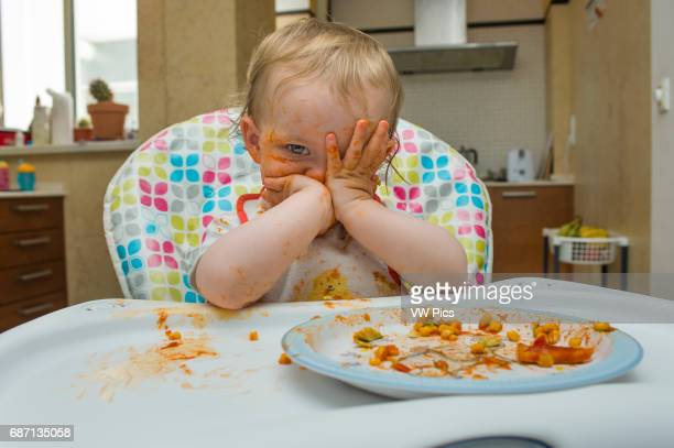 A baby girl eats a meal of sweet corn and tomato sauce in a messy manner and plays with her food on a high chair in her home [MR Maude Saez...