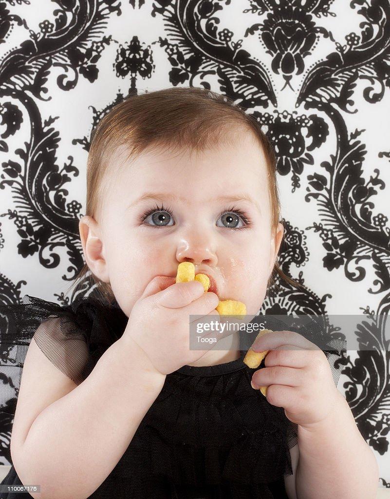 Baby girl feeding herself : Stock Photo