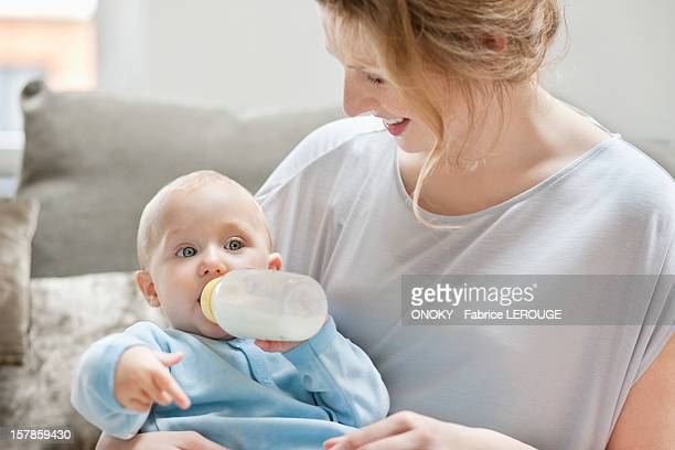Baby girl feeding on milk with a milk bottle