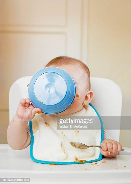 Baby girl (6-7 months) holding bowl to face sitting in high chair