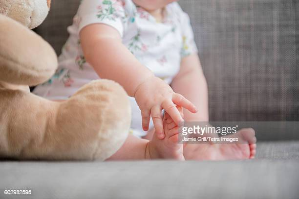Baby girl (12-17 months) holding foot