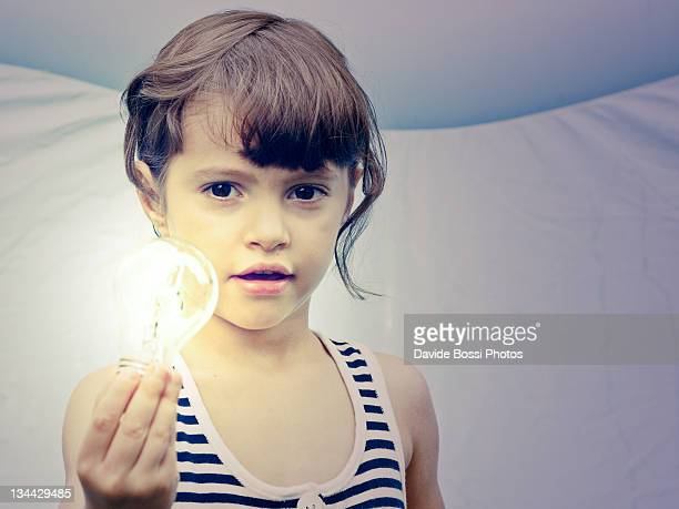 Baby girl holding light bulb