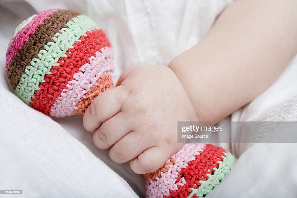 Baby girl holding rattle : Stock Photo