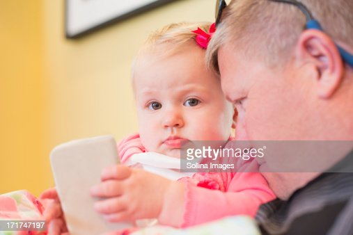 Baby girl holding smartphone with dad closed toher : Stock Photo