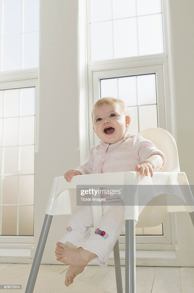 A baby girl in a high chair : Stock Photo