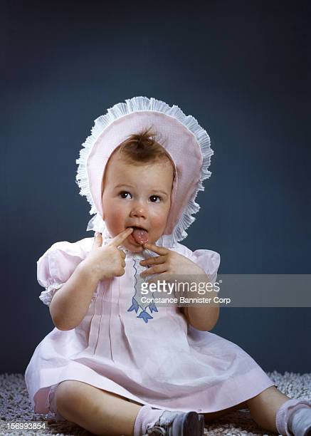 A baby girl in a pink dress and bonnet licking her fingers New York City USA 12th December 1944