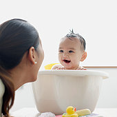 Baby girl in bathtub laughing at mother