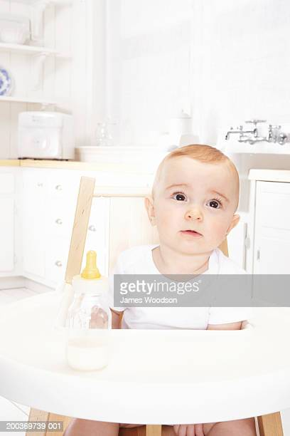 Baby girl (6-9 months) in high chair, close-up