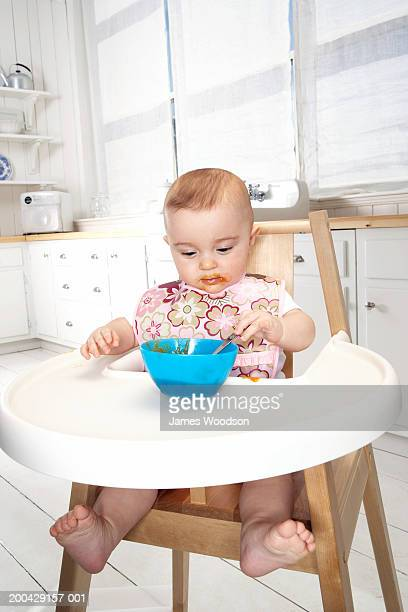 Baby girl (5-7 months) in high chair eating from bowl