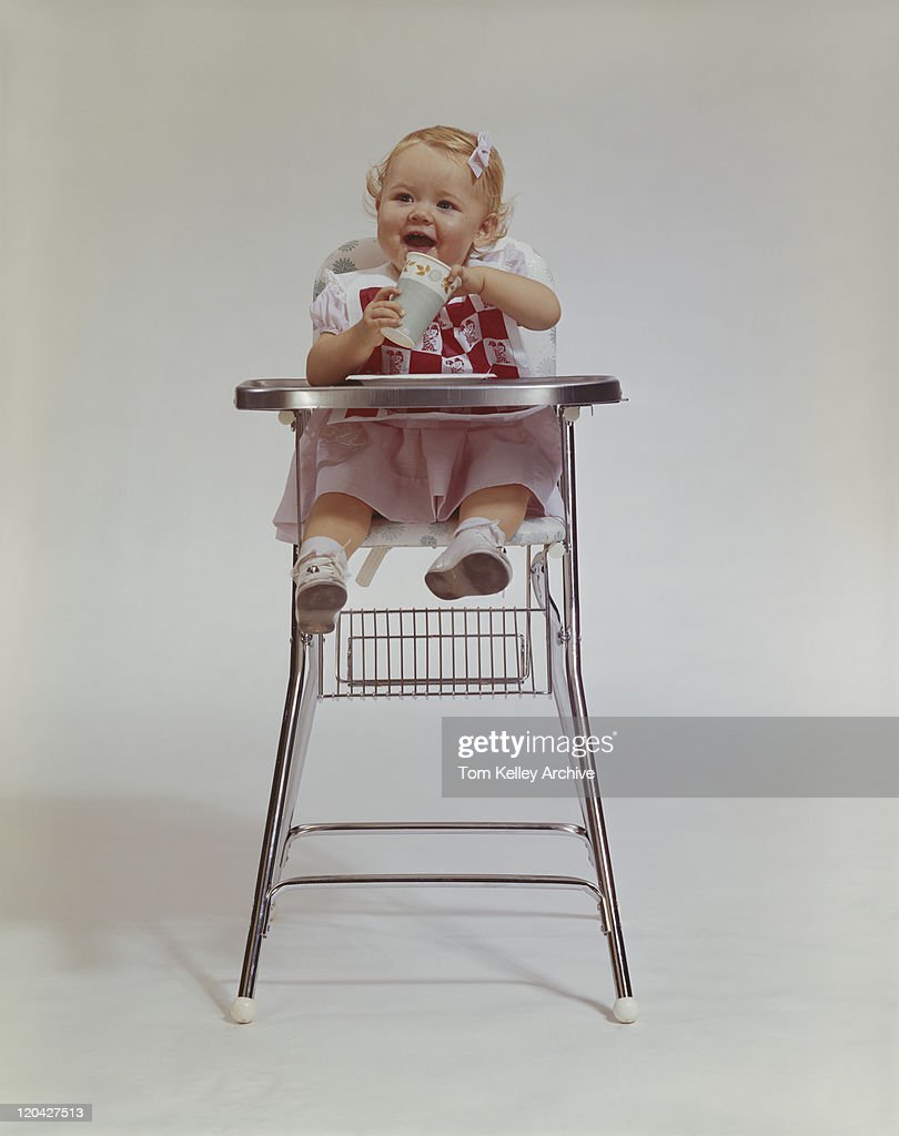 Baby Girl Drinking Bottle In High Chair Stock Photo Getty Images
