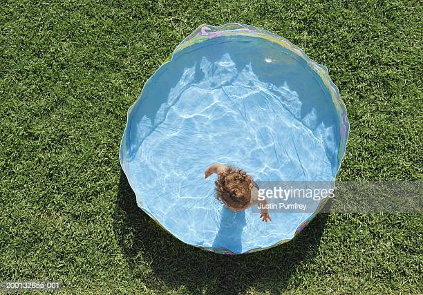 Baby girl (21-24 months) in paddling pool, overhead view