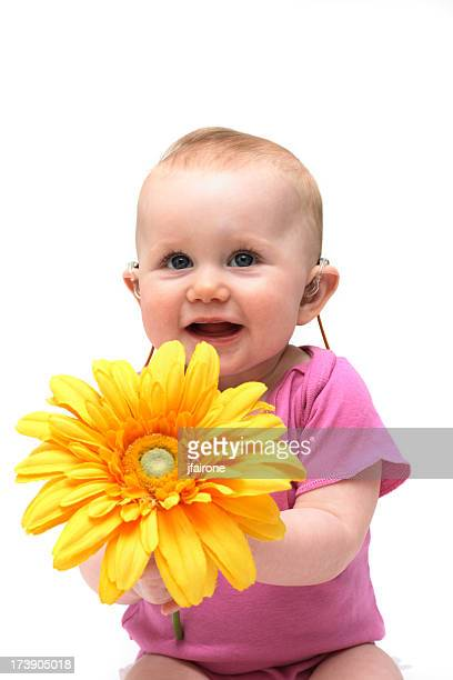 A baby girl in pink holding a flower