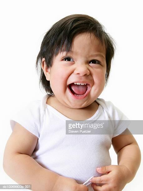 Baby girl (18-23 months) laughing, studio shot