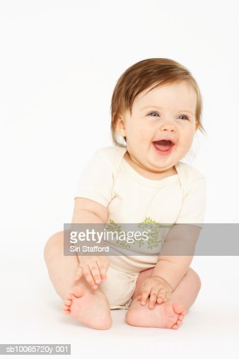 Baby girl (6-9 months) laughing, white background : Stock Photo