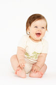 Baby girl (6-9 months) laughing, white background