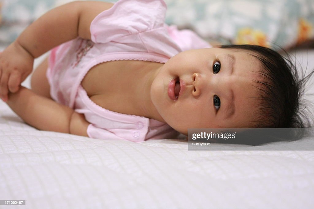 Baby girl laying on bed : Stock Photo