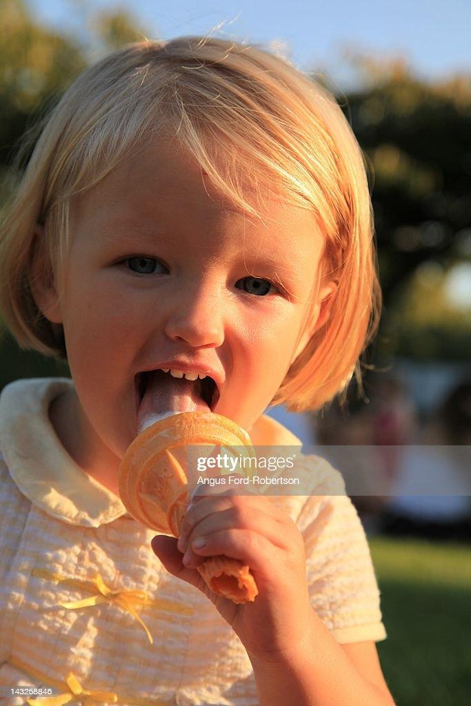 Baby girl licks ice-cream : Stock Photo