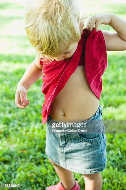 Baby girl lifting shirt up, looking curiosly at abdomen