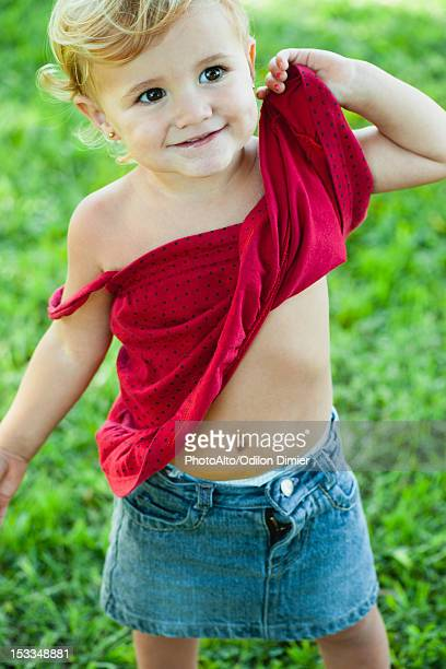 Baby girl lifting shirt up, portrait