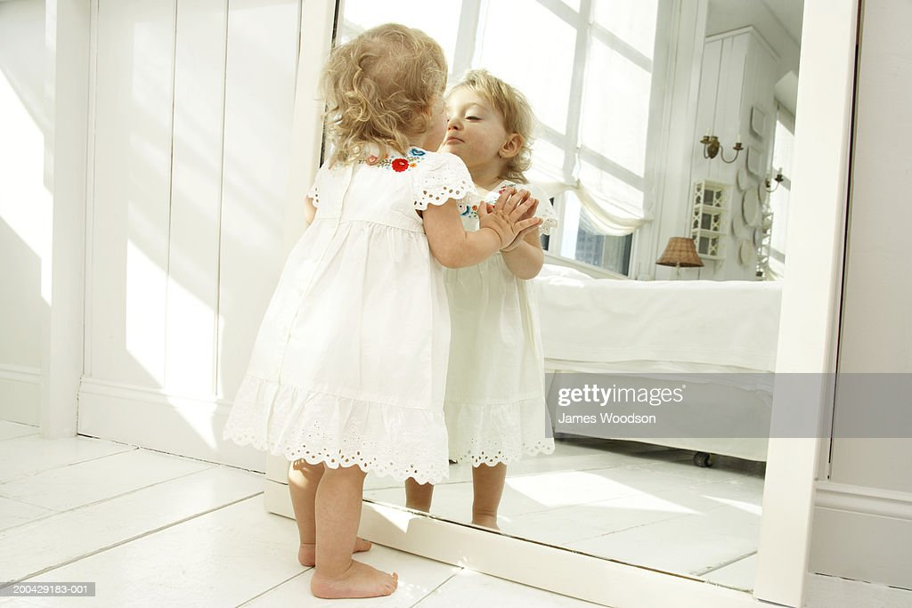 Baby girl (18-24 months) looking in mirror, hands pressed on glass