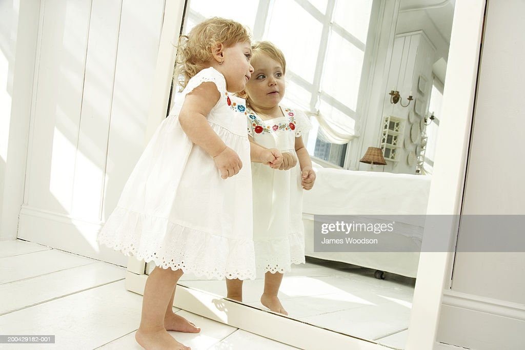 Baby girl (18-24 months) looking in mirror, side view
