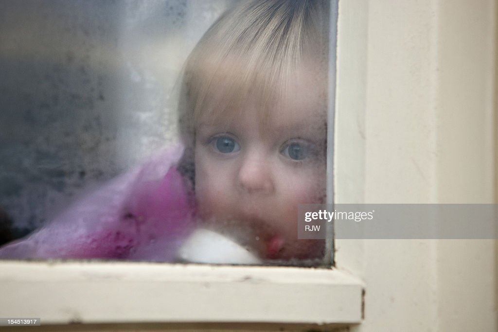 Baby Girl looking out of Window : Stock Photo