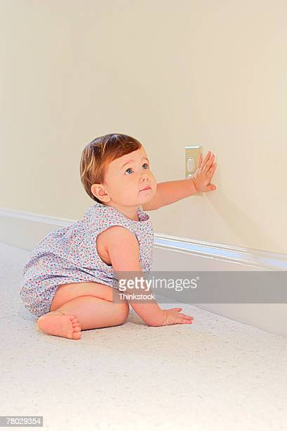 A baby girl looks up as if she got caught trying to touch an electrical outlet with safety plugs in it.