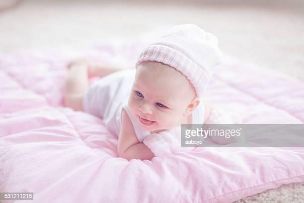 Baby girl lying a su estómago usar sombrero y mittens