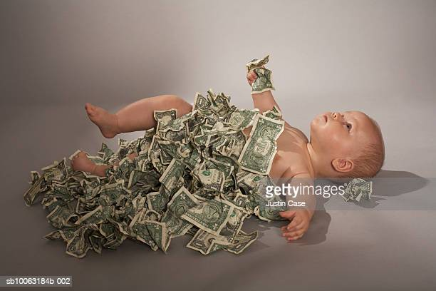 Baby girl (5 months) lying down covered with us dollar bills