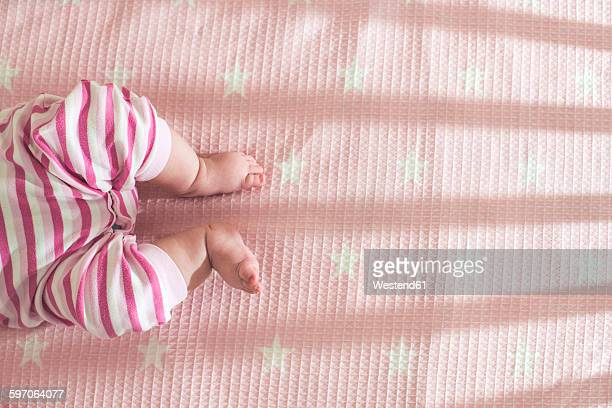 Baby girl lying in a cot, partial view